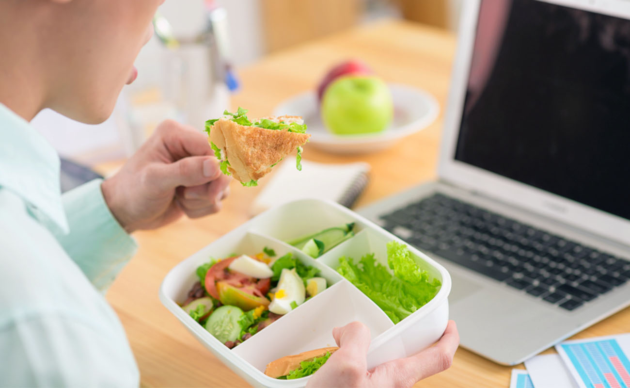 Man Eating from Lunch Box in Office